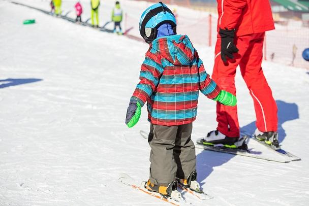 Dziecko uczy się jeździć na nartach